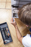 Man with tools repair the fridge Stock Photos