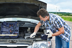 Man with tools repairs broken car Stock Photography