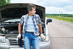 Man with tools waiting to help near broken car Royalty Free Stock Image