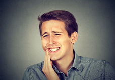 Man with toothache crown problem about to cry from pain. Closeup portrait young man with sensitive toothache crown problem about to cry from pain touching royalty free stock photography