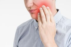 Man with a toothache, pain in the human body. On a gray background with red dot Stock Photo