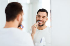 Man with toothbrush cleaning teeth at bathroom Royalty Free Stock Images