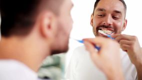 Man with toothbrush cleaning teeth at bathroom stock footage