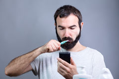 Man with Toothbrush and Smartphone Stock Photos