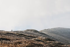 Man on top of frost hill, walking up. Amazing scenery of people. And mountain Royalty Free Stock Photos
