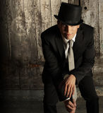 Man in top hat. Fashion portrait of young male model in top hat and cane against grunge wall background Stock Photo