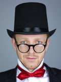 Man in top hat with bow. Handsome young man in top hat and dinner jacket with red bow and glasses or spectacles, studio background Stock Photo