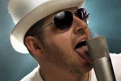 Man in Top-hat licks microphone.  Stock Photos