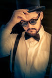 Man with Top Hat and Steampunk Glasses Retro Portrait. Gentleman portrait, young bearded man wearing steampunk glasses, bowtie and top hat stock image