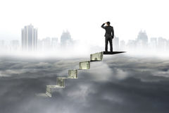 Man on top of money stairs looking at cityscape cloudscape Royalty Free Stock Images