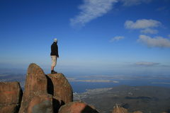 Man on top of a Mountain. Man standing on top of Mount Wellington, viewing the city of Hobart Tasmania below. There is copy space in the image for text royalty free stock image