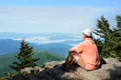 Man a top of mountain enjoying beautiful foggy mountain landscape. Man sitting a top of mountain relaxing. and looking at beautiful foggy mountain landscape Royalty Free Stock Photography