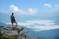 Man a top of mountain enjoying beautiful foggy mountain landscape. Man standing a top of mountain relaxing. and looking at beautiful foggy mountain landscape Royalty Free Stock Photography
