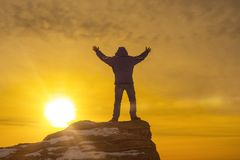 Man at the top of the mountain, holding up his hand, against the background of a dramatic sky in the sunset. Concept success, victory, career growth Royalty Free Stock Photo