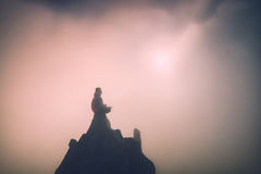 Man on the top of a mountain. Instagram stylization. Man meditating in sitting yoga position on the top of a mountain above clouds at sunset light. Zen Stock Photo