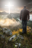Man on top of the mountain looking at the Christian Cross. Man on the edge of a cliff looking toward a cross stock photos