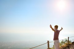 Man on top of a mountain looking for horizon. Young man with raised hands on top of Vesuvius mountain looking for the horizon Royalty Free Stock Photography