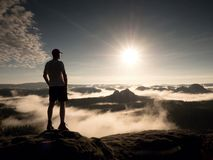 Man at the top of a mountain looking the misty landscape. Feel free Stock Photo