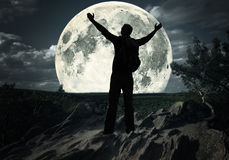 Man on the top of mountain looking at the moon. Man standing on the top of mountain looking at the moon Royalty Free Stock Photo