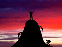 Man on top of the mountain and the other people to climb up. Man on top of the mountain and the other people to climb up on fiery orange background. Rock Royalty Free Stock Image