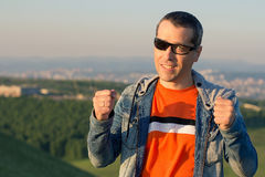 The man at top of the mountain rejoices to success. Winner. Royalty Free Stock Image