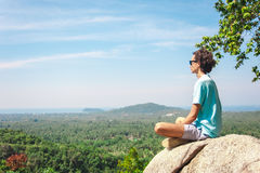 Man on top of mountain sitting on the rock watching picturesque view Royalty Free Stock Photo