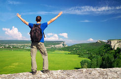 Man on top of mountain. Tourism concept. Tourist on the high rock Royalty Free Stock Images