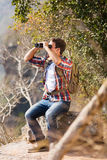 Man top mountain. Young man sitting on top of the mountain and using binoculars Stock Image