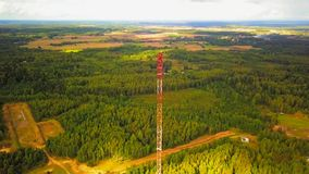 Man on top of old communications tower. A man controlling a drone camera from the top of an old communications tower stock video footage