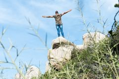 Man on the top of a rock formation with his arms in the air stock photos