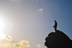 Man in the top of a rock. A man in the top of a rock just moments before the sunset Royalty Free Stock Photo