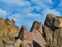 Man on top of a rocky mountain cliff Royalty Free Stock Photo