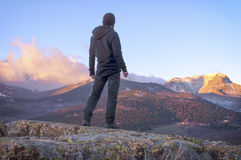 Man on top watching a beautiful sunrise in the sunny snowy mount Stock Photos