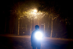 Man with torch at night. Silhouette of man with torch in the night with background of trees stock photo
