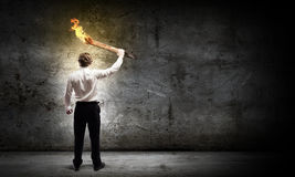 Man with torch. Young businessman holding burning torch in hand royalty free stock image
