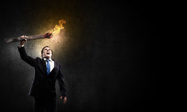 Man with torch. Young businessman holding burning torch in hand royalty free stock photography