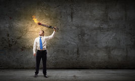 Man with torch. Young businessman holding burning torch in hand royalty free stock photos