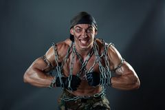 Man tore the chain. A man with huge muscles. He tearing chains that bind his body Stock Image