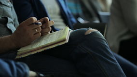 The man in torn blue jeans holding a notebook on his lap. He is quite young or middle aged male, he has wedding ring on his finger, he's wearing a gray shirt stock footage