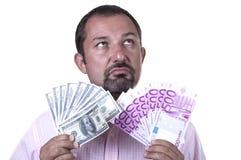 Man torn between dollars and euros Stock Photo
