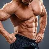 Man with torso muscles showing ok sign. Muscular man with beautiful torso muscles showing ok sign. Midsection of shirtless man pointing at abs isolated on grey stock photo