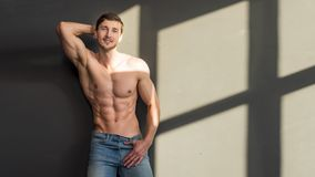 Man with torso, muscular macho with six packs, dark background. Macho on pensive face with muscular figure, sportsman stock photo