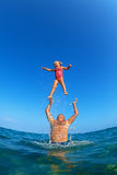 Man tossing up child with water splashes in beach Stock Photography