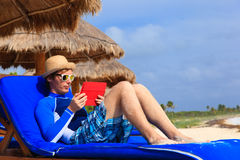 Man with touch pad on tropical beach Stock Photo