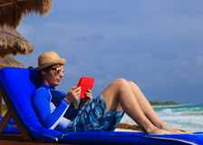 Man with touch pad on tropical beach Royalty Free Stock Photography