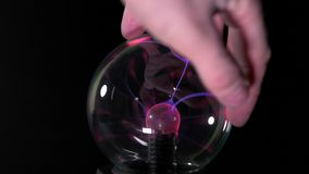 Man touches the ball with lightning stock footage
