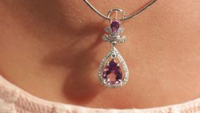 A man touches a silver pendant with a magenta diamond on a beautiful female neck with his finger.Jewellery.Shallow depth. Of field stock video footage