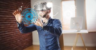 Man touching clock and gears seen through VR glasses. Digital composite of Man touching clock and gears seen through VR glasses Royalty Free Stock Image