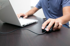 Man touching computer mouse and typing on a pc Stock Photography
