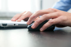 Man touching computer mouse and typing on a pc Royalty Free Stock Photos